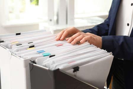 Femme prenant des documents du dossier dans l'archive, gros plan Banque d'images