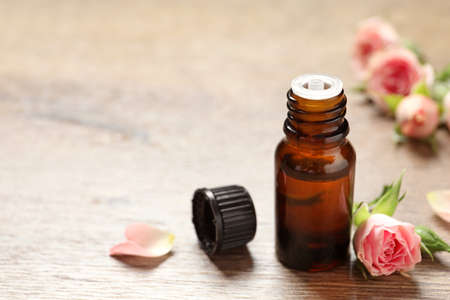 Bottle of rose essential oil and fresh flowers on wooden table, space for text