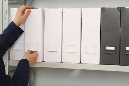 Woman taking folder with documents from shelf in archive, closeup