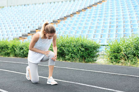 Woman in sportswear suffering from knee pain at stadium