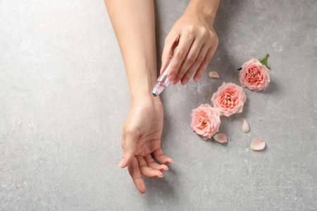 Woman applying rose essential oil on wrist and flowers at grey table, top view