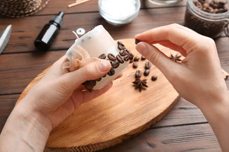 Woman decorating handmade candle with coffee beans at wooden table, closeup