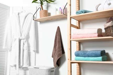 Toallas limpias y bata cerca de la pared blanca en el interior del baño moderno
