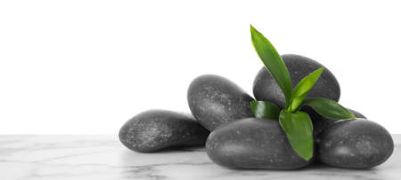 Black spa stones with bamboo on table against white background. Space for text