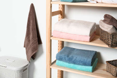 Shelving unit with clean towels near white wall in modern bathroom interior
