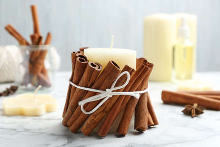 Candle with cinnamon sticks on marble table