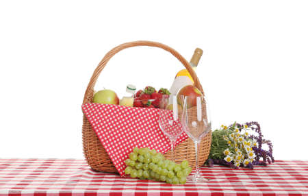Picnic basket with wine and food on tablecloth against white background
