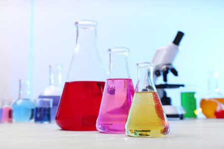 Différentes fioles coniques avec des échantillons sur table en laboratoire de chimie