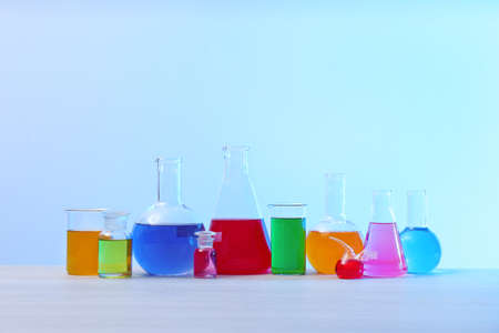 Different glassware with samples on table against light background. Solution chemistry Banque d'images