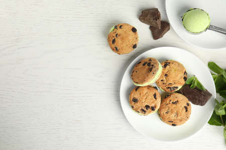 Sweet delicious ice cream cookie sandwiches served on table, flat lay. Space for text