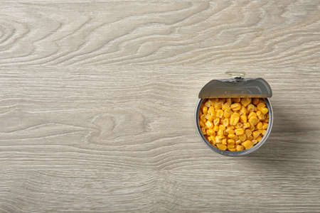 Open tin can of corn kernels on wooden background, top view. Space for text