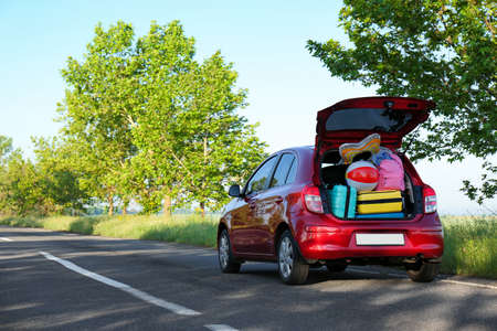 Family car with open trunk full of luggage on highway. Space for text