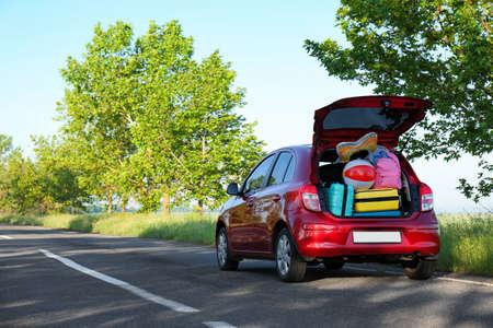Gezinsauto met open kofferbak vol bagage op snelweg. Ruimte voor tekst