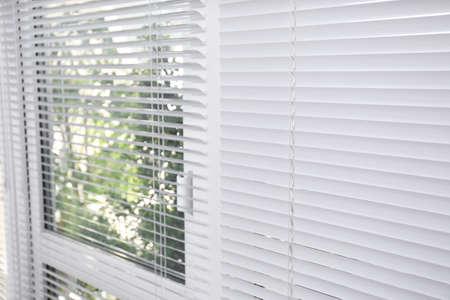 Fenster mit geschlossenen weißen horizontalen Jalousien als Hintergrund