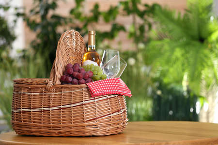 Picnic basket with wine, glasses and grapes on wooden table against blurred background, space for text