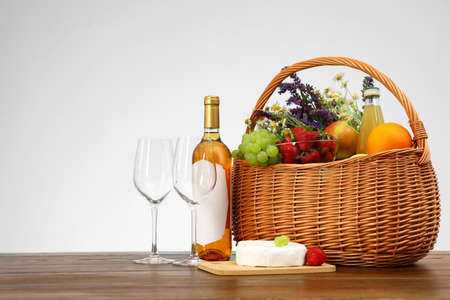 Picnic basket with wine and products on wooden table against white background. Space for text