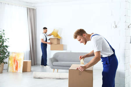 Moving service employee sealing cardboard box with adhesive tape in room