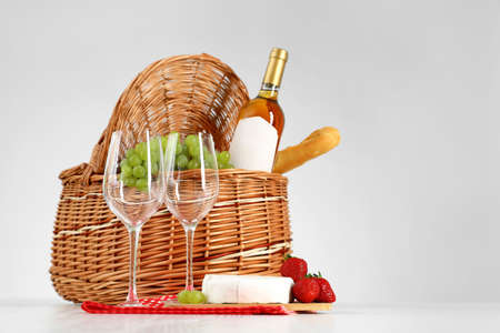 Picnic basket with wine, glasses and products on white background Stock Photo