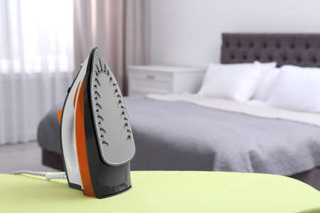 Modern electric iron on board in bedroom, space for text. Laundry day
