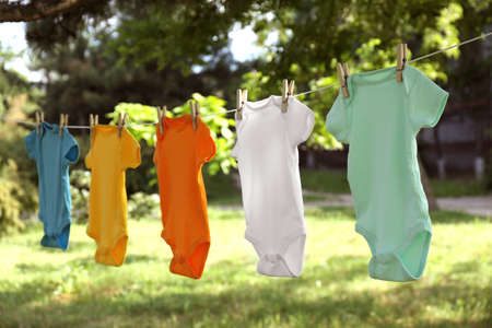 Colorful baby clothes hanging on clothes line outside