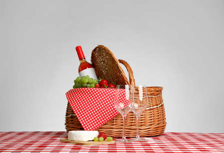 Picnic basket with wine and products on checkered tablecloth against white background