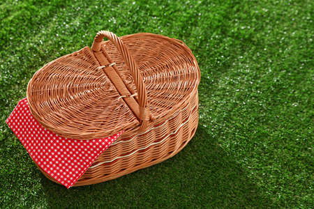 Closed picnic basket with napkin on grass, space for text Stock Photo