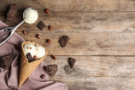 Flat lay composition with delicious ice cream in waffle cone on wooden table, space for text