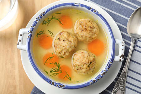 Bowl of Jewish matzoh balls soup on wooden table, top view