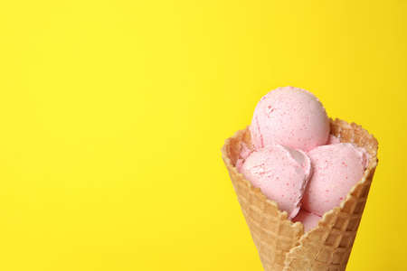 Delicious ice cream in waffle cone on color background, space for text