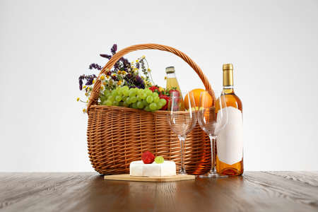 Picnic basket with wine and products on wooden table against white background
