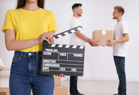 Operator holding clapperboard during the production indoors, closeup