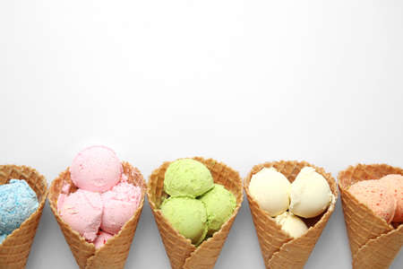 Composition with delicious ice creams in waffle cones on white background, top view Imagens