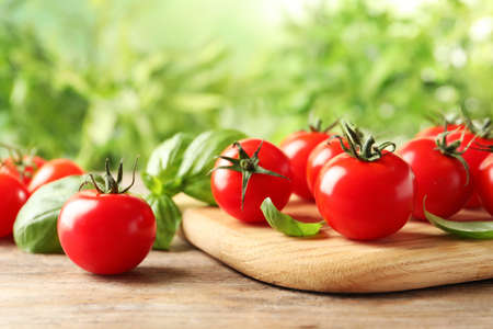 Board with fresh cherry tomatoes on wooden table