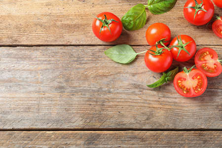 Fresh cherry tomatoes on wooden background, flat lay. Space for text