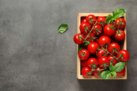 Crate with fresh cherry tomatoes on stone background, top view. Space for text Reklamní fotografie