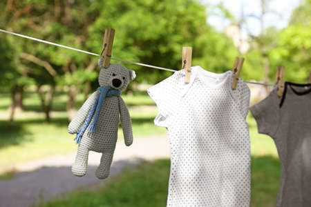 Baby clothes and toy bear hanging on clothes line outside