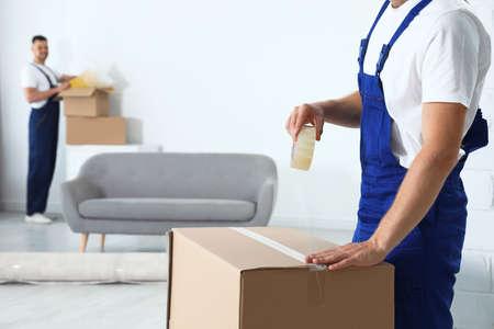Empleado del servicio de mudanza sellando la caja de cartón con cinta adhesiva en la habitación, primer plano Foto de archivo