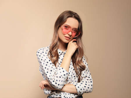 Portrait of beautiful young woman with heart shaped sunglasses on color background