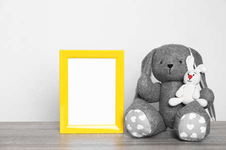 Photo frame and adorable toy bunnies on table against light background, space for text. Child room elements