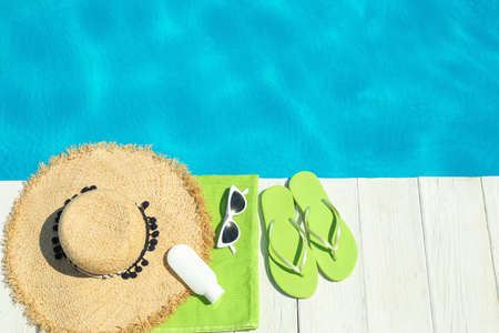 Flat lay composition with beach accessories on wooden deck near swimming pool. Space for text