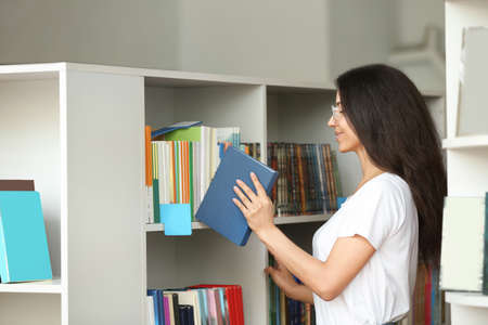 Young woman putting book on shelf in library