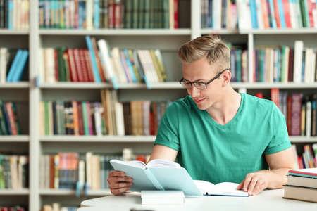 Młody człowiek czytanie książki przy stole w bibliotece. Miejsce na tekst Zdjęcie Seryjne