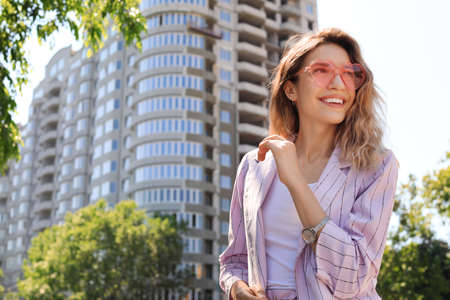 Portrait of happy young woman with heart shaped glasses in city on sunny day. Space for text