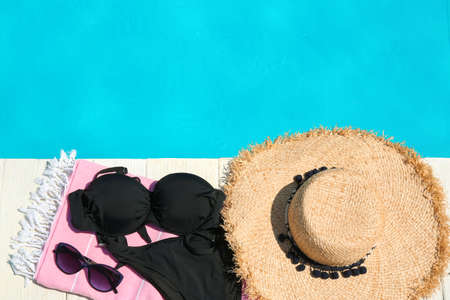Beach accessories on wooden deck near swimming pool, flat lay. Space for text