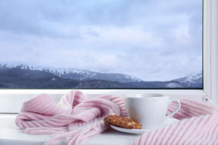 Hot drink, cookie and scarf near window with view of winter mountain landscape Foto de archivo