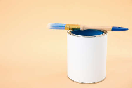 Open blank can of paint with brush on color background. Space for text