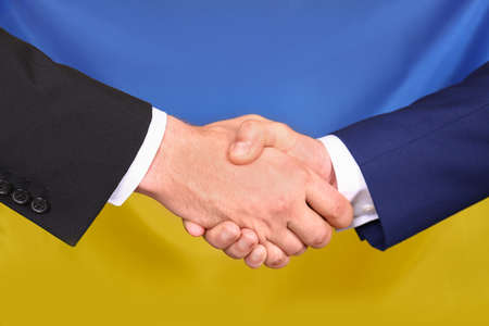 Men shaking hands against Ukrainian national flag, closeup. International relationships