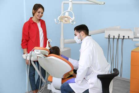 Professionele tandarts die met weinig patiënt in moderne kliniek werkt Stockfoto