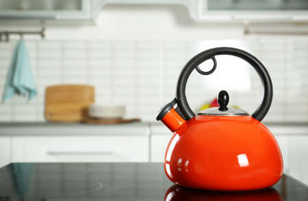 Modern kettle with whistle on stove in kitchen, space for text 写真素材
