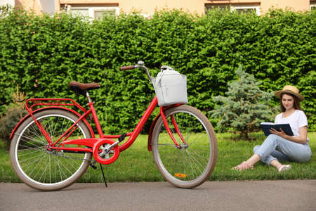 Young woman sitting near modern bicycle on grass outside